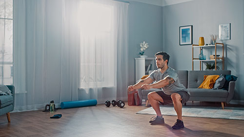 A man performs a squat exercise in the hardwood paneled, living room of his apartment.